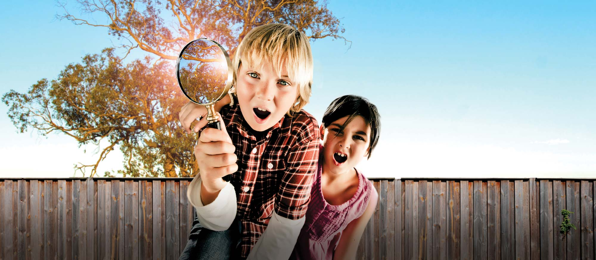 Children exploring Backyard Adventures with magnifying glasses