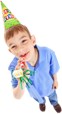 Young boy wearing birthday hat and blowing noisemaker