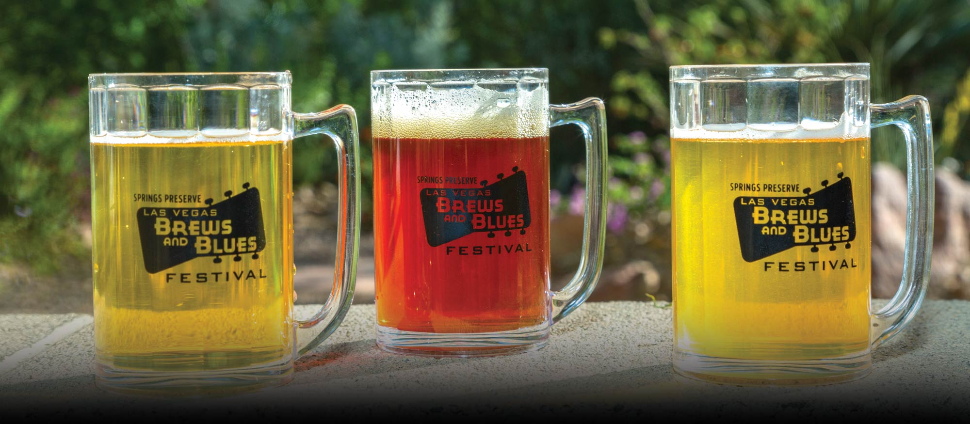 Three types of beer in Brews & Blues Festival mugs.