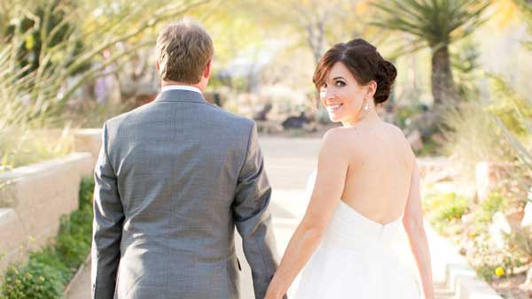 Bride looks back at Springs Preserve wedding. Photo by J. Anne Photography.