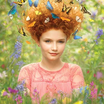 Young girl in Butterfly Habitat with butterflies in her hair.