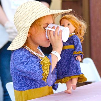 Young girl drinking from tea cup and holding doll
