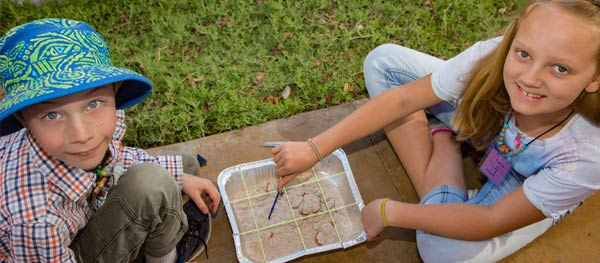 Children completing archaeology project at camp