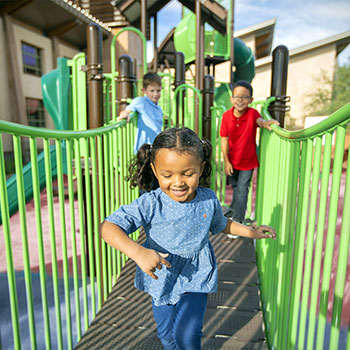 Children crossing a bridge at the Springs Preserve playground